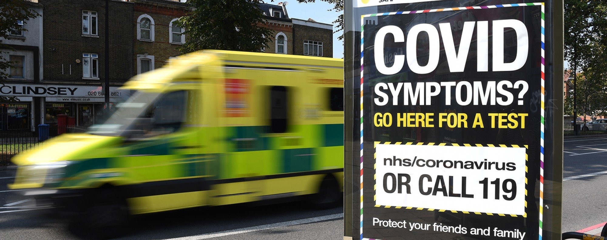 An ambulance drives past a Covid-19 helpline sign in south London. Photo: EPA-EFE