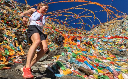 Megan Kimmel is surrounded by Tibetan flags on her way to victory in the Yading Skyrun. Photo: MRSWS/Albert Jorquera