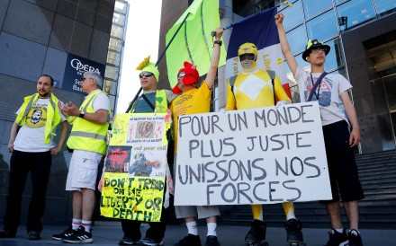 "Protesters, some of them claiming to have been seriously injured during the last six months Yellow Vest demonstrations, hold a placard reading in French ""Join our forces for a more just world"". Photo: AFP"
