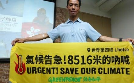 Climber Wong Wai-kin displays a Greenpeace banner to save the environment while sharing his climbing experience. Photo: Jonathan Wong