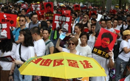 """Hongkongers march from Causeway Bay to the government headquarters in Admiralty on June 9, in protest against the proposal to amend the city's extradition laws to allow the transfer of fugitives to mainland China. The message on the yellow umbrella calls on the people to oppose the """"evil law"""". Photo: Xiaomei Chen"""