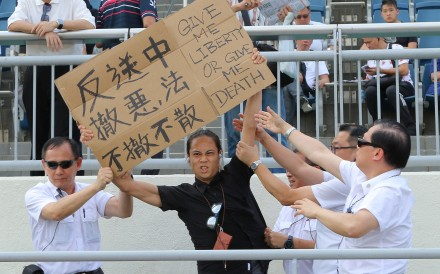A protester holds up a sign at Sha Tin on Sunday. Photos: Kenneth Chan