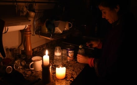 A woman using candles in her home in Montevideo on Sunday. Photo: AFP