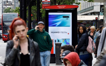 Pedestrians on their mobile phones near a Huawei advertisement at a bus stop in central London in April. Photo: AFP