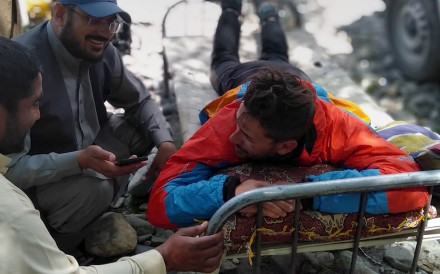 A mountaineer receives initial treatment following his rescue, at a helipad in the town of Imit. Photos: Gilgit Baltistan regional police department