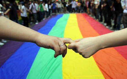 Gay and lesbian activists form a human chain around a rainbow flag during celebrations marking the fourth annual International Day Against Homophobia (Idaho) in Hong Kong on May 18, 2008. Photo: Ted Aljibe/AFP