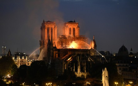 Firefighters douse flames rising from the roof at Notre-Dame Cathedral in Paris. Photo: AFP