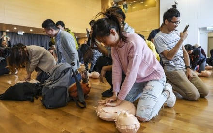 Participants in a Fire Services Department activity learn to perform CPR and use an automated external defibrillator, in Tseung Kwan O in December 2018. Photo: Roy Issa