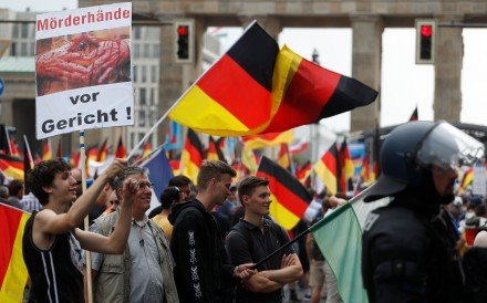 Alternative for Germany (AfD) demonstrators wave German flags and hold a placard reading 'Killer's hands in trial!' in front of the Brandenburg Gate in Berlin. Photo: AFP