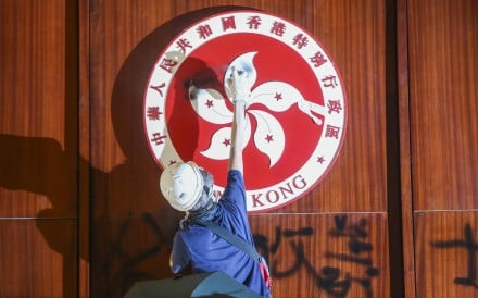 A protester defaces the Hong Kong emblem in the Legislative Council chamber. Photo: Winson Wong