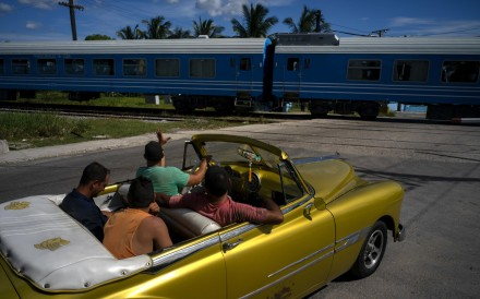A driver in an American classic car waves as the first train using new equipment from China rides past, in Havana. Photo: AP