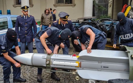 Policemen carry an air-to-air missile seized in northern Italy on Monday. Photo: Italian police via AFP