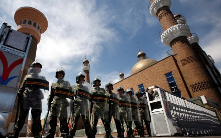 Chinese paramilitary police in riot gear stand guard at the entrance to a large mosque in the centre of Urumqi, in China's Xinjiang Autonomous Region, in July 2009. Photo: Reuters