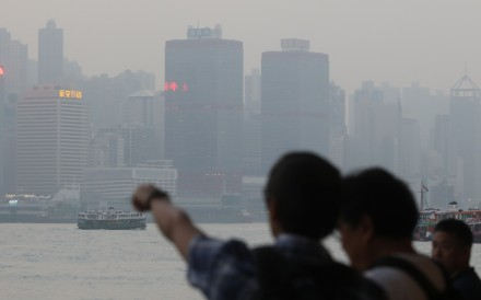 """Tourists looking out to Victoria Harbour last November amid high air pollution levels, which were rising towards """"serious"""" levels in the city on Wednesday. Photo: Sam Tsang"""