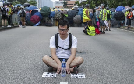 A protester sits down on a Sha Tin street to make a point about non-violence, during a rally against the now-shelved extradition bill, on July 14. The posters on the ground call on demonstrators to give up violence and protest peacefully. Photo: Edmond So