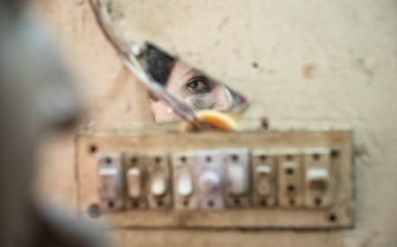 Shanta, a hijra from Bangladesh, applies her make-up in front of a fragment of mirror in the attic she rents with other transgenders. Photo: Zigor Aldama