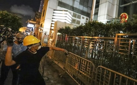 A protester takes aim at the national emblem outside Beijing's liaison office in Hong Kong on Sunday. Photo: Felix Wong