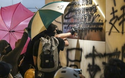 Protesters deface the wall of the central government's liaison office in Hong Kong on Sunday. Photo: Edmond So