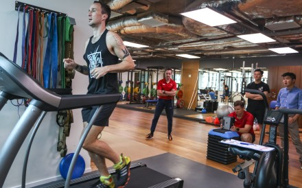 SCMP reporter Patrick Blennerhassett gets his gait analysis tested at Joint Dynamics as coaches Erwan Desvalois and David Jacquier look on. Photo: Xiaomei Chen
