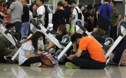 Anti-government protesters sit behind a barricade of trolleys and check their smartphones at the Hong Kong International Airport on August 13. Photo: Felix Wong
