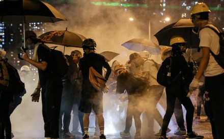 Protesters rush to put out smoking tear gas canisters fired by police in Tin Shui Wai on August 5. Photo: Rachel Cheung