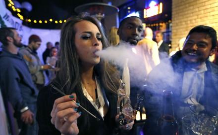 A young woman smokes marijuana at a party in Denver, Colorado. Photo: AP