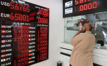A man checks rates at a currency exchange shop in Istanbul last year. The currency market is still feeling its way through the ripple effects of the trade war. Photo: AP