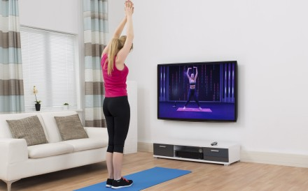 Home workouts such as those led by Fiit app trainer Chessie King (on television) are part of a burgeoning digital fitness industry. Photo: Alamy