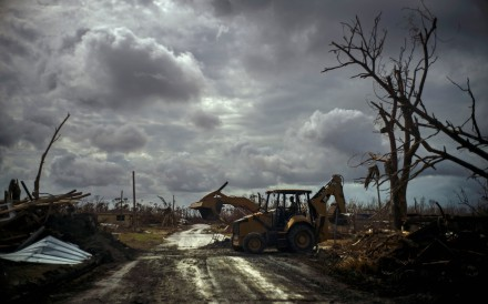 Mos Antenor, 42, drives a bulldozer while clearing the road after Hurricane Dorian Mclean's Town, Grand Bahama. Photo: AP Photo