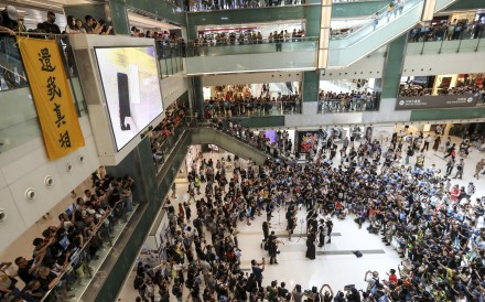 Hundreds gathered for a 'singing protest' in a Sha Tin shopping centre, with some demonstrators taking their cause directly to retailers judged to have links to their opponents. Photo: Nora Tam