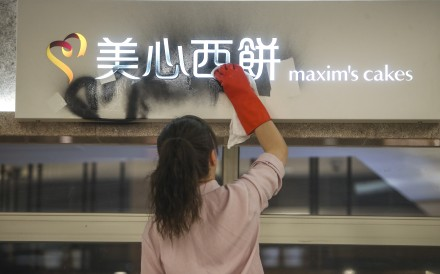 An employee tries to remove graffiti from a sign at a Maxim's cake shop in New Town Plaza in Sha Tin. Photo: Winson Wong
