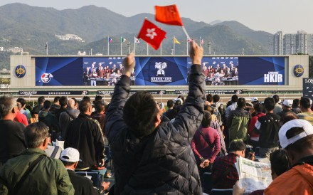 A racing fan waves the flags of Hong Kong and China during the Hong Kong International Races. Photo: Sam Tsang