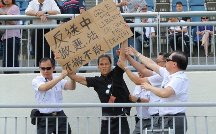 A pro-democracy protester holds up a sign at the Sha Tin races in June. Photos: Kenneth Chan