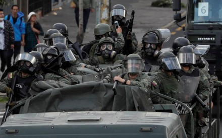 Ecuadorean troops move through the streets of Quito after the curfew started. Photo: EPA
