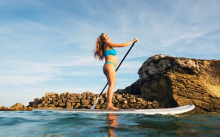 A pregnant woman doing stand-up paddle surfing.