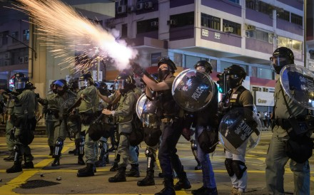 Police fire tear gas on Nathan Road on Sunday night. Photo: AFP