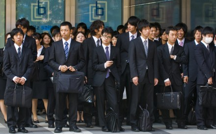 Japanese office workers stands outside an office building in Tokyo Japan. Microsoft in Japan trialled a four day work week. Photo: Shutterstock