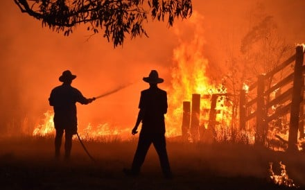 Residents defend a property from a bush fire at Hillsville, 350km north of Sydney. Photo: AFP