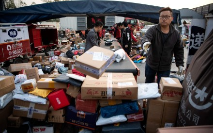 Workers sort out packages at a delivery company warehouse to be delivered to customers on November 12, the day after Singles' Day. Photo: AFP
