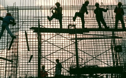 Workers erect a reinforcement grid of iron bars for a concrete wall of a power substation in Manila. Photo: AFP