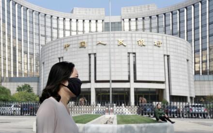 A woman walks past the headquarters of the People's Bank of China in Beijing on September 28, 2018. China's central bank made a number of small rate cuts in November this year, easing fears that it was constrained in delivering monetary stimulus. Photo: Reuters
