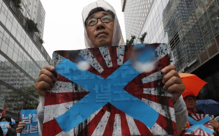 South Korean protesters hold Japanese rising sun flags during a rally in Seoul on August 15, 2019. File photo: AP