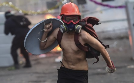 A demonstrator wearing a helmet runs with a makeshift shield during a protest in Santiago. Photo: AFP