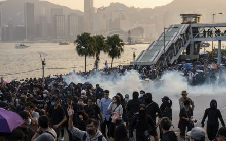 Riot police fire tear gas to disperse demonstrators during a protest in Tsim Sha Tsui on December 1. Photo: Bloomberg