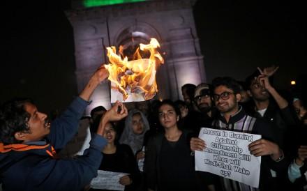 Demonstrators burn a copy of Citizenship Amendment Bill during a protest in New Delhi on December 12, 2019. Photo: Reuters