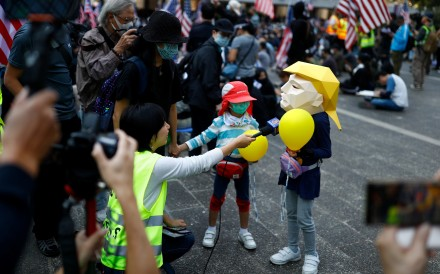 """A child wearing a mask of US President Donald Trump is interviewed during a """"march of gratitude"""" to the US consulate in Hong Kong on December 1. Although the anti-government movement has been marred by violence, it has also shown tremendous creativity. Photo: Reuters"""