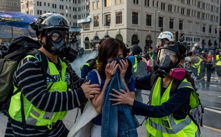 First-aid volunteers help a woman affected by tear gas during a march in Kowloon, Hong Kong, on December 1. Respect for medical personnel has been a basic barometer of humanitarian conduct for centuries, and has been coded in international law since the first Geneva Convention in 1864. Photo: AFP