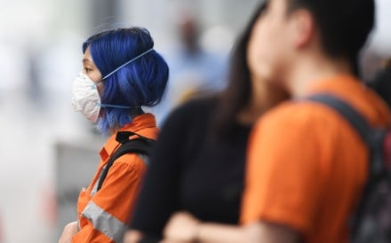 A pedestrian in Melbourne wears a face mask to protect herself from haze triggered by devastating bush fires across the Australian states of Victoria and New South Wales, on January 14. Photo: AAP Image/DPA
