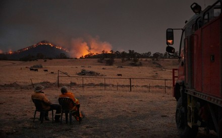 "Rural Fire Service volunteer firefighters watching as the New South Wales ""megafire"" approaches the outskirts of the town of Tumbarumba in New South Wales. Photo: Handout via AFP"