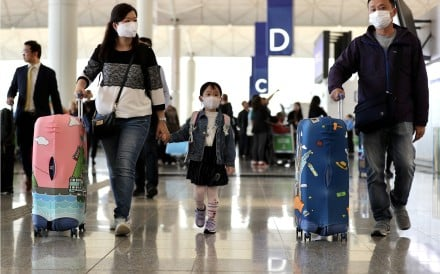 A young family in face masks at the check-in hall of the Hong Kong International Airport on January 22, as China ramped up efforts to contain a new respiratory virus that has killed at least 26 people and infected nearly 900. Photo: Bloomberg